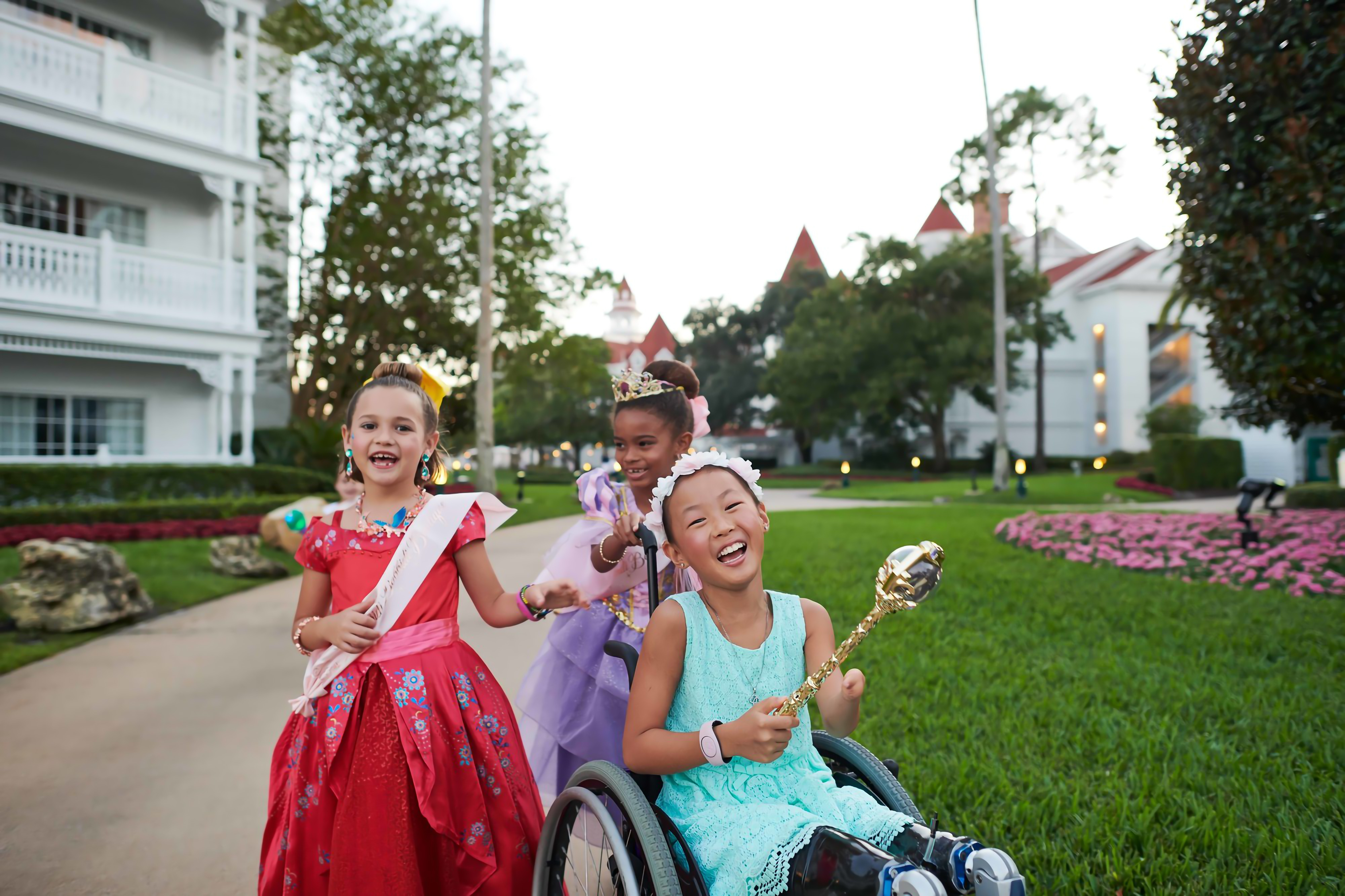 Three little girls in dresses smiling at the camera.